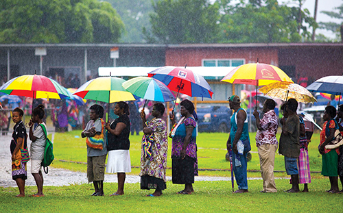Bougainville locals wait in the rain for medical screening and treatment at a community health engagement as part of Pacific Partnership 2015.